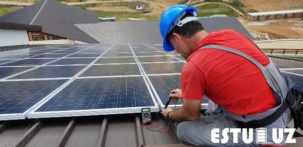 Técnico instalando paneles solares en una vivienda.