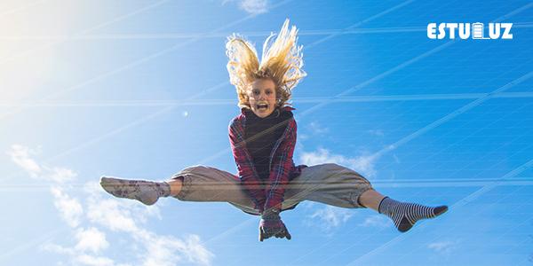 Chica saltando con son entre placas solares